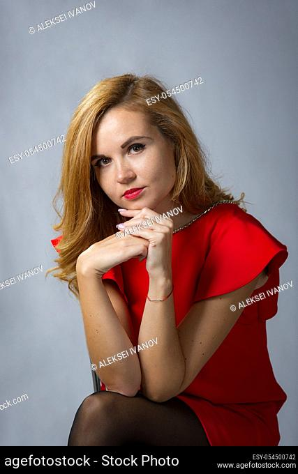 Spectacular girl in red dress looks pensively in the frame