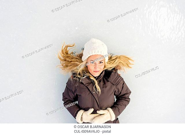 Overhead view of mid adult woman lying on ice looking at camera smiling
