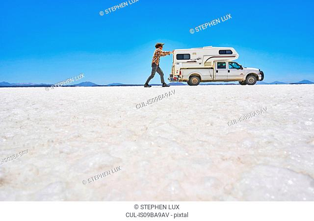 False perspective image of boy on salt flats, pretending to push recreational vehicle, vehicle in background, Salar de Uyuni, Uyuni, Oruro, Bolivia