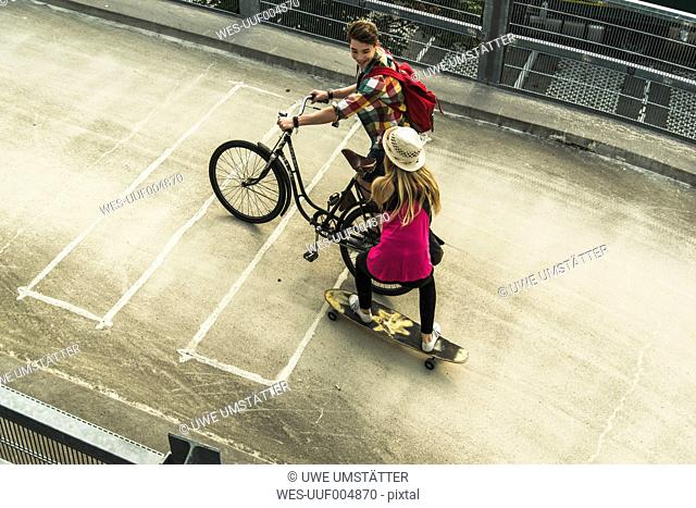 Young couple with bicycle and skateboard