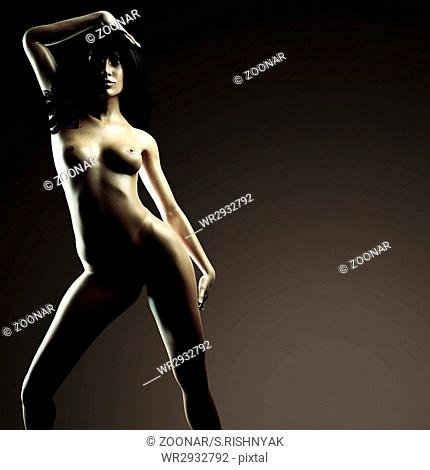 Beautiful naked young woman in the dark studio
