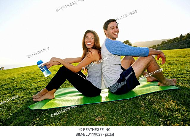 Couple sitting on yoga mat in park