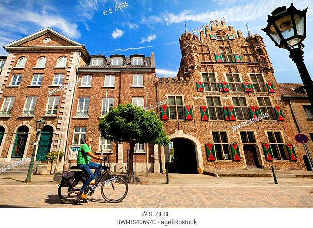 cyclist in front of town hall, and patrician house 'Haus zu den fuenf Ringen', Germany, North Rhine-Westphalia, Lower Rhine, Goch