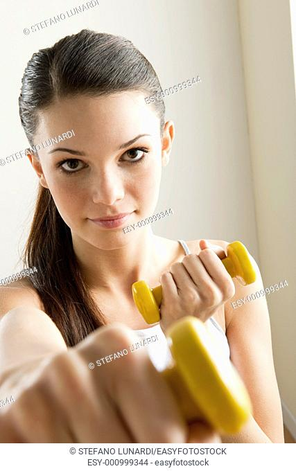 Young woman excercising with dumbells