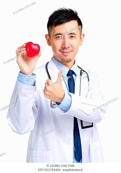 Doctor holding heart shape toy and thumb up
