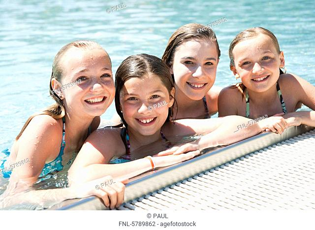 Four smiling girls in swimming pool