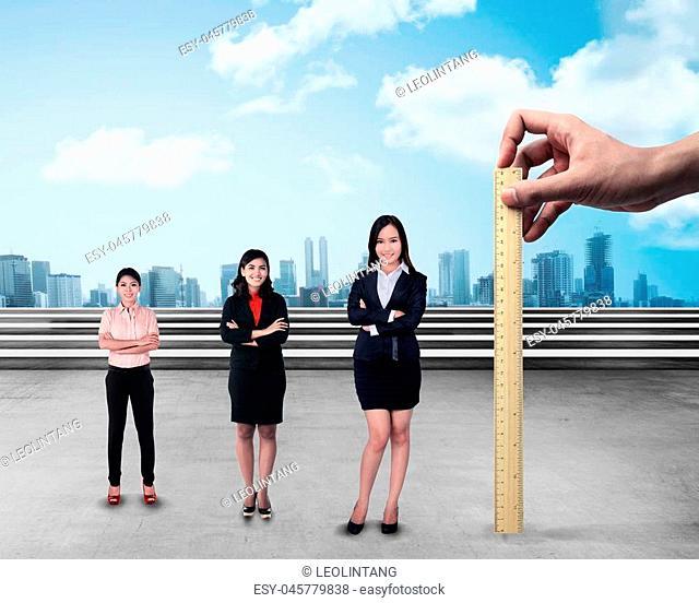 Hand holding wooden ruler, mesuring employee performance. Working appraisal concept
