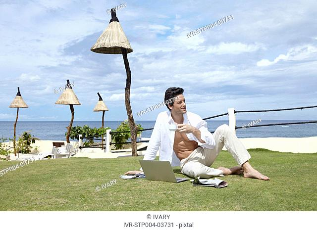 A man sitting on the grass with a laptop