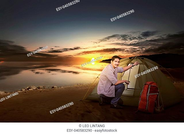 Smiling asian traveler man with backpack set up a tent beside the lake