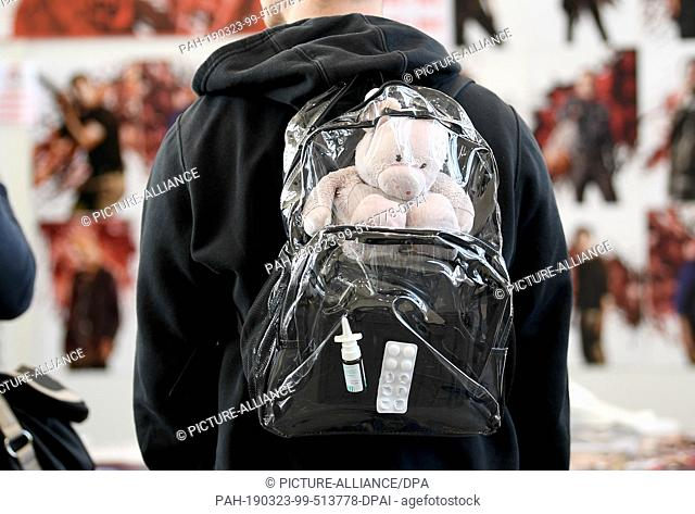 """23 March 2019, Berlin: A young man carries a cuddly toy, nasal spray and tablets in a transparent rucksack at the """"""""Walker Stalker Con"""""""" at Messe Berlin"""