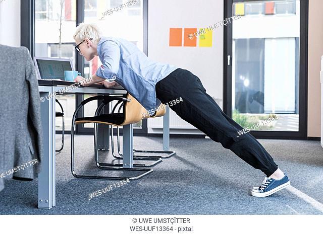 Businesswoman in office doing push ups on desk