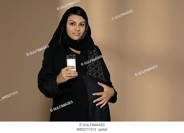 Pregnant woman holding glass of milk and touching abdomen,portrait