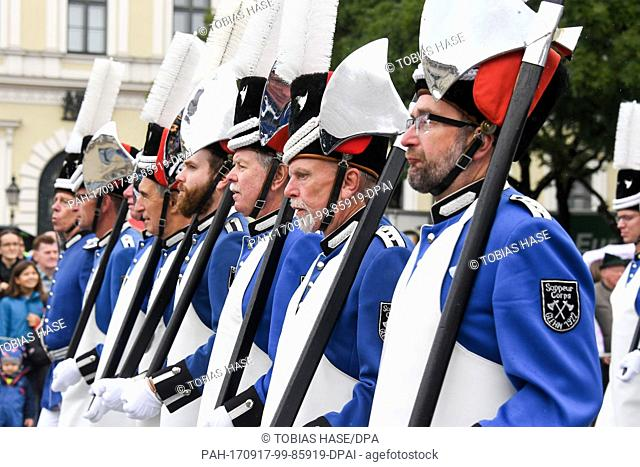 A group of people dressed in traditional attire carries axes during the traditional costume parade in a coach in Munich, Germany, 17 September 2017