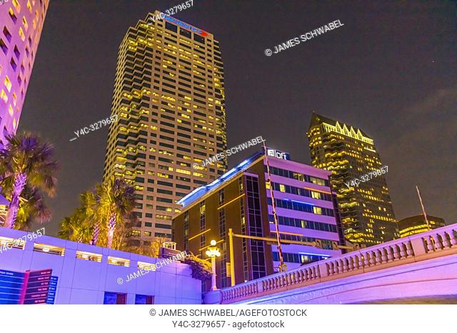 Downtown Tampa Florida buildings lit up at night with colorful lights as seen from the Tampa Riverwalk