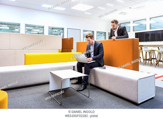 Businessman sitting in conversation pit, colleague watching him