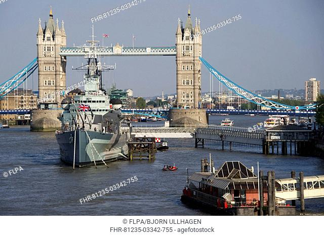 View of HMS Belfast museum ship moored on river in city, Tower Bridge, River Thames, London, England, april