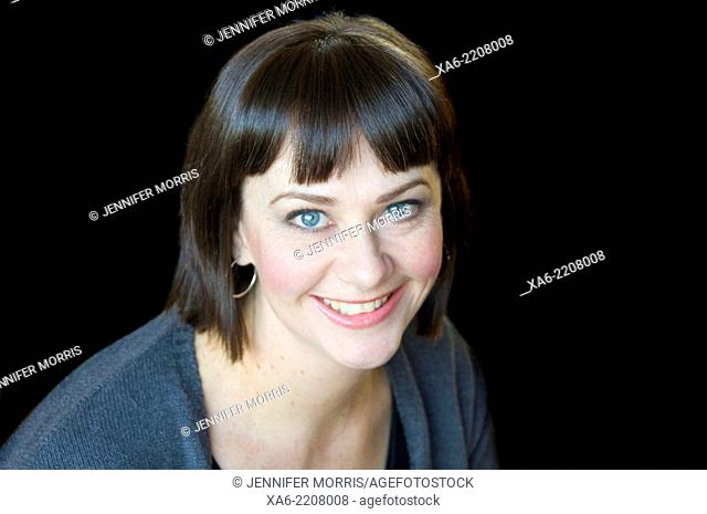 A 30-something woman smiles at the camera against a black background