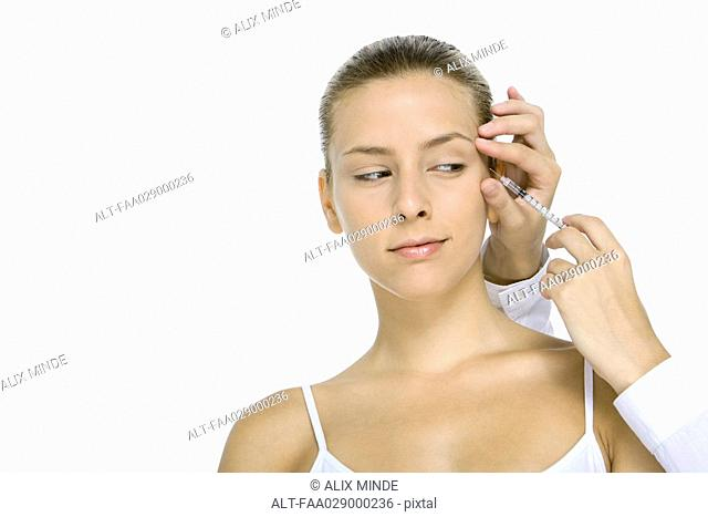 Woman receiving Botox injection, looking at syringe