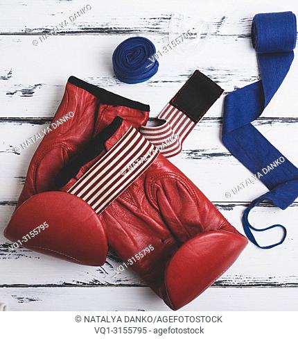 pair of leather red boxing gloves, blue bandage and silicone mouth cap on a white wooden background