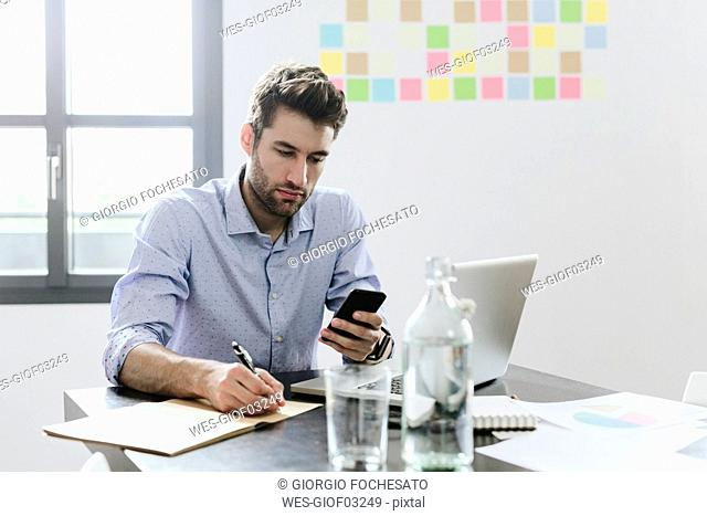 Young businessman working in office, using smartphone and laptop