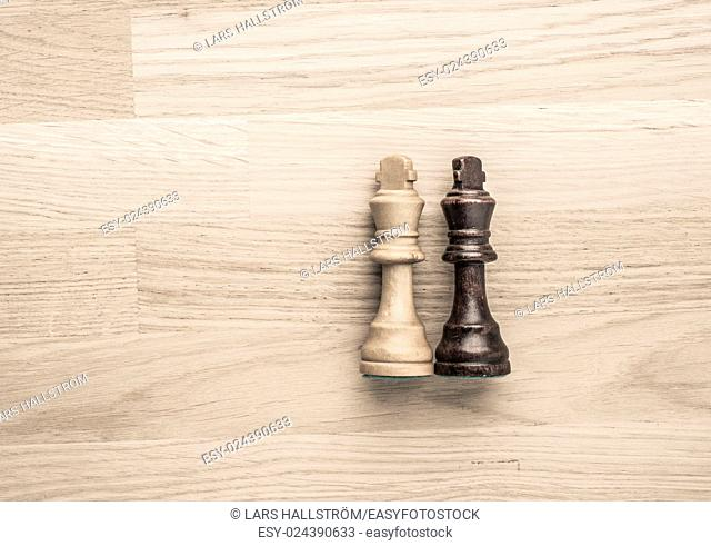 Black and white chess kings lying down. Concept of draw, competition and conflict with no winner