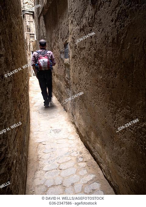 Rear view of man walking on narrow street, Fez, Morocco