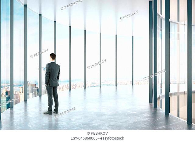 Thoughtful businessman standing in modern glass corridor interior with city view and daylight. 3D Rendering
