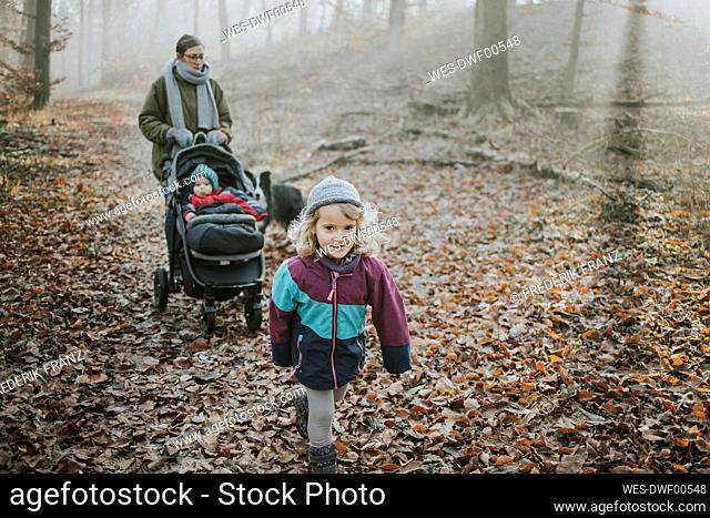 Mother with daughters and border collie during forest walk in autumn