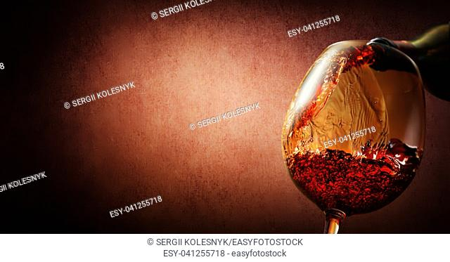 Wine pouring from bottle on textured burdundy background
