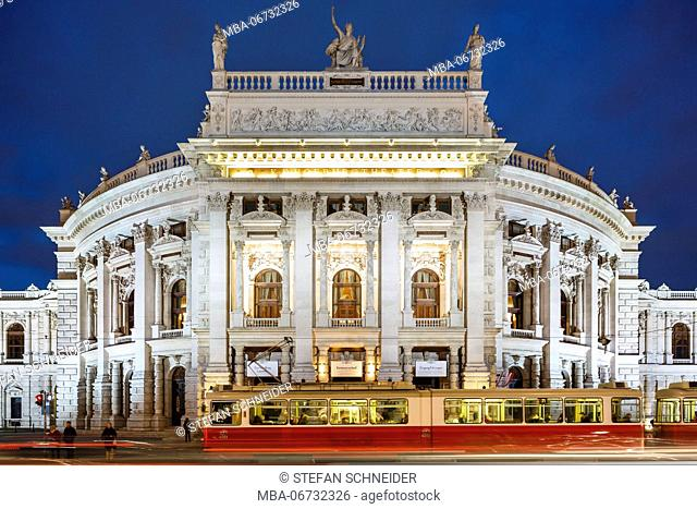 Blue hour at Burgtheater in Vienna with motion blur by tramway in the foreground