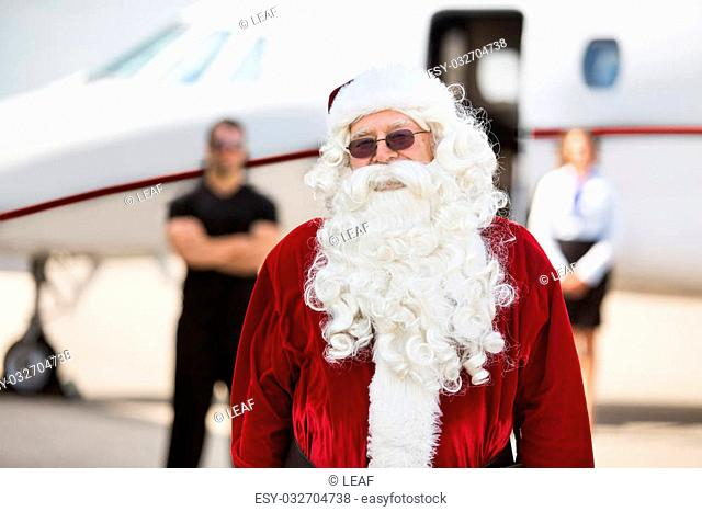 Portrait of man in Santa costume standing against private jet at airport terminal