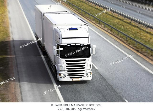 White refrigerated trailer truck transports perishables goods on motorway, motion blur, above view
