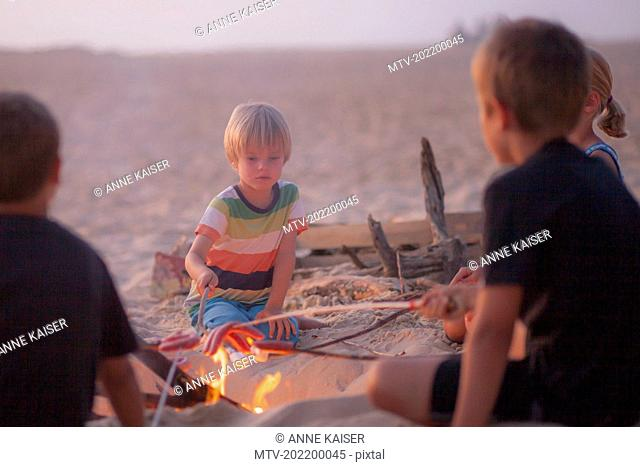 Boy with his friends enjoying camping on the beach, Lit-et-Mixe, Aquitaine, France