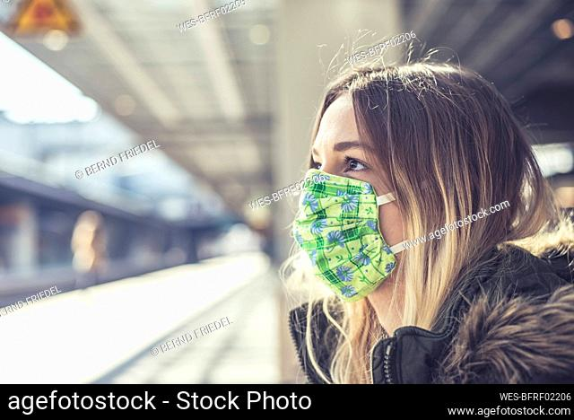 Portrait of young woman wearing mask at station platform