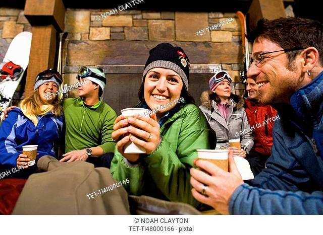 Group of skiers hanging out at fireplace