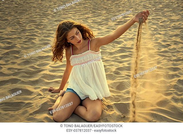 Teen girl on the beach playing with sand in the wind