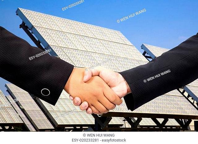 Businessman shaking hand before Solar power plant