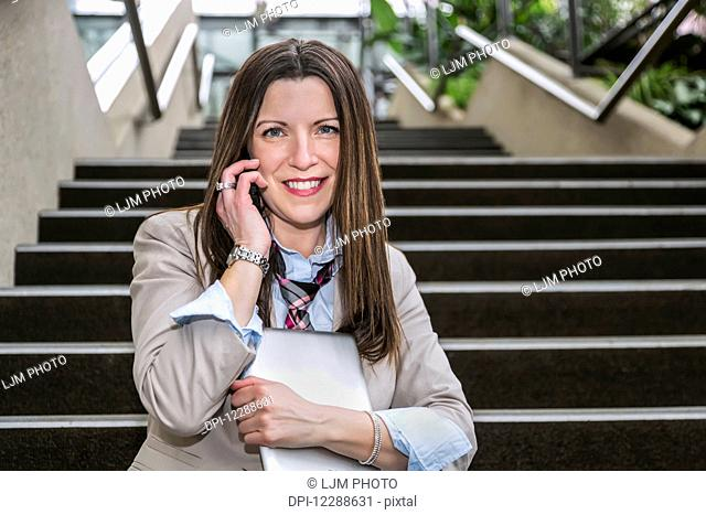 Mature business woman talking on her cell phone and holding a tablet while sitting on stairway in the atrium of an office building; Edmonton, Alberta, Canada
