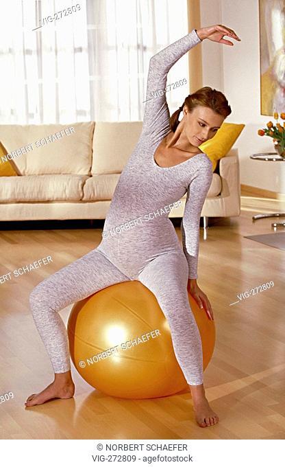 portrait, pregnant woman makes gymnastic sitting on a big yellow ball  - DEUTSCHLDEU, 19/06/2006