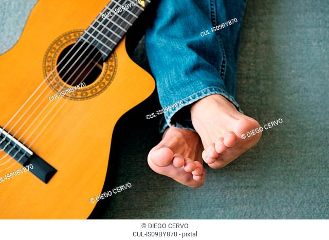 Guitarist with legs outstretch beside guitar on floor