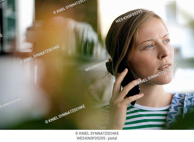 Portrait of young woman on cell phone in a cafe