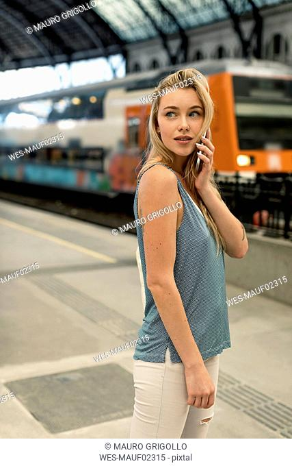 Young woman on cell phone at the train station looking around