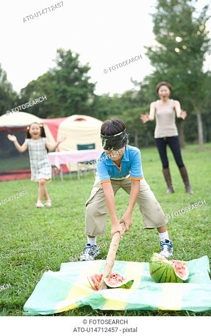 Boy Splitting Watermelon with Blindfold