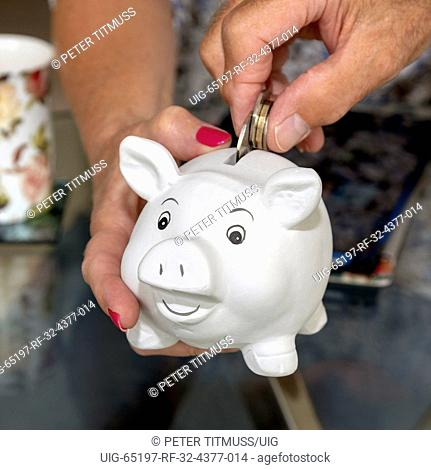 Putting money into a white piggy bank being held by womans' hand