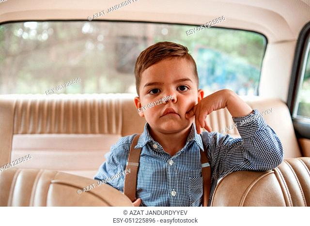 Caucasian little boy in vintage clothes sitting inside a retro car