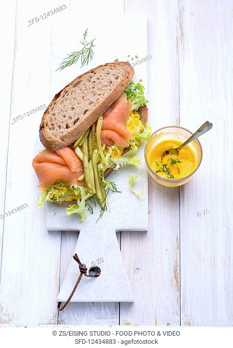 A salmon sandwich with gherkins and carrot cream