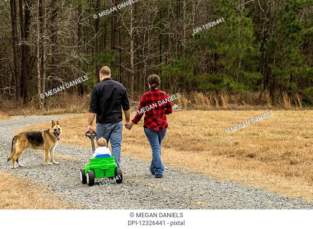 A mother with brown curly hair wearing a black and red plaid shirt and a father wearing a black shirt pull their one-year-old son in a green wagon on a gravel...