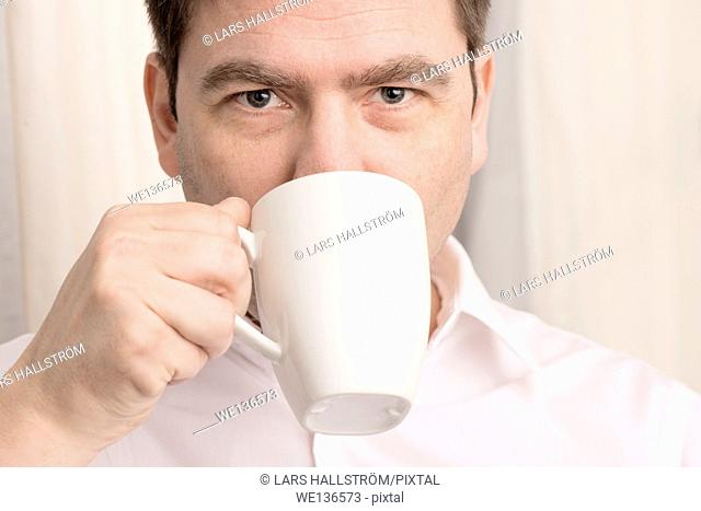 Close up of man drinking from coffee cup and looking in camera