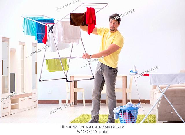 Handsome man husband doing laundering at home