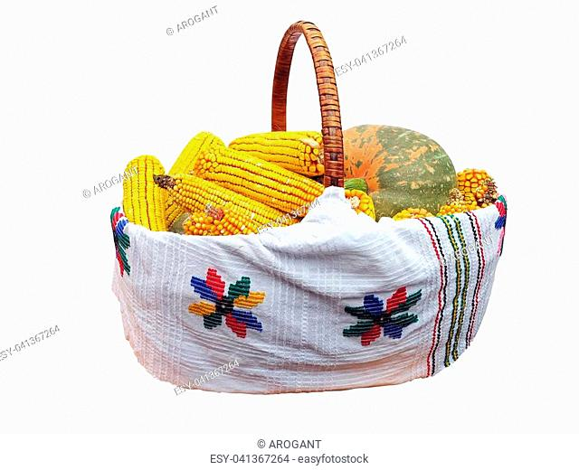 Fresh corn and pumpkin vegetable in basket isolated over white